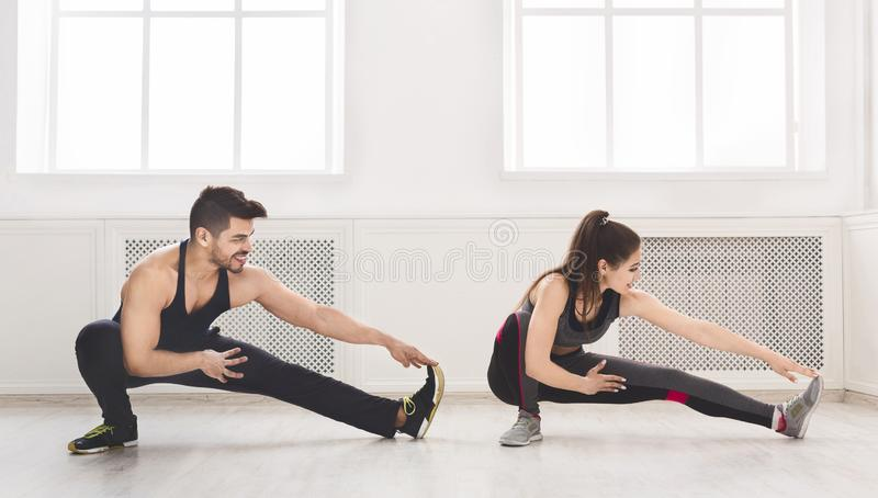 Sporty couple stretching legs before training in studio. Panorama, copy space royalty free stock photo