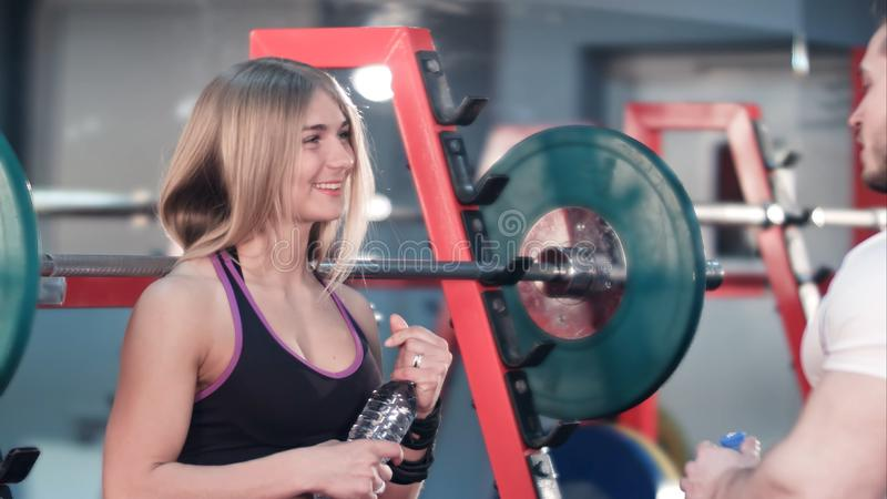 Sporty couple talking and drinking water after exercises in the gym stock photography