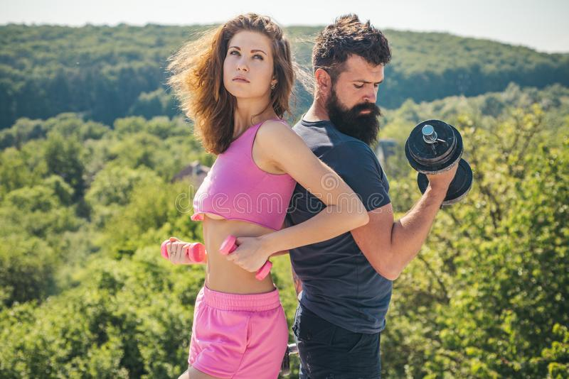 Sporty couple training outdoor. perfect body muscle. dumbbell lifting. sport and fitness. bearded man and woman with fit stock image