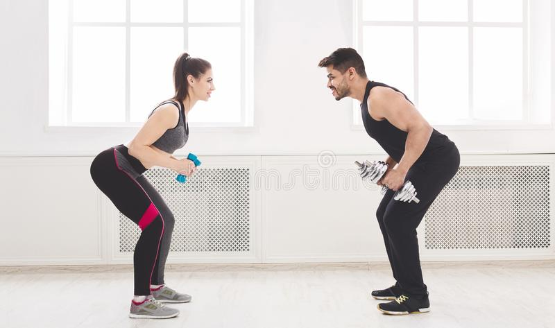 Sporty couple working out with dumbbells in front of each other. Studio background, copy space stock photo
