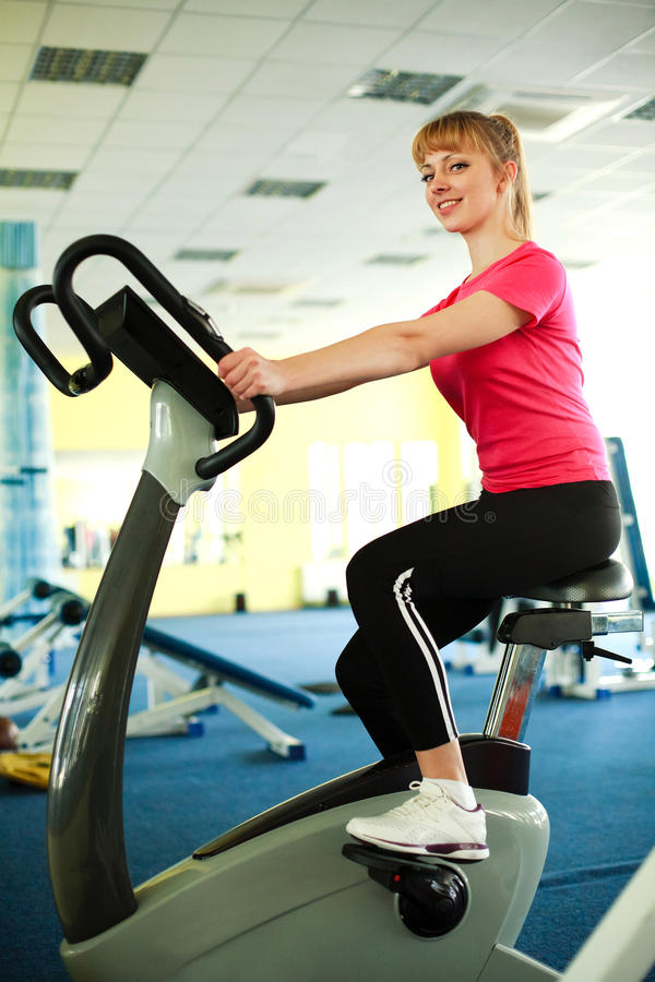 Sporty cute girl exercising on the bicycle stock photos