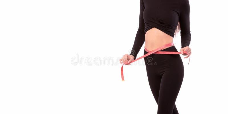 Милая женщина в черном костюме изолированном на белой предпосылке закрывает вверх sporty и красивого женского тела Женщина с лент стоковое изображение rf