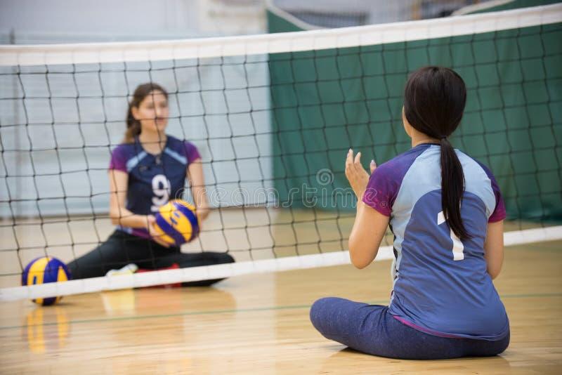 Sporty dla niepełnosprawni Dwa młodej kobiety siedzi na podłodze i bawić się siatkówkę Kobieta z ponytail zdjęcie stock