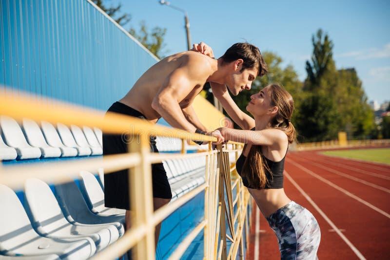 Sporty dobierają się w miłości ściska na atletyka śladu polu fotografia stock