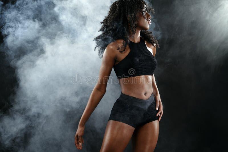 Sporty dysponowana czarna skóry kobieta, atleta ćwiczy robi sprawności fizycznej na ciemnym tle obrazy royalty free