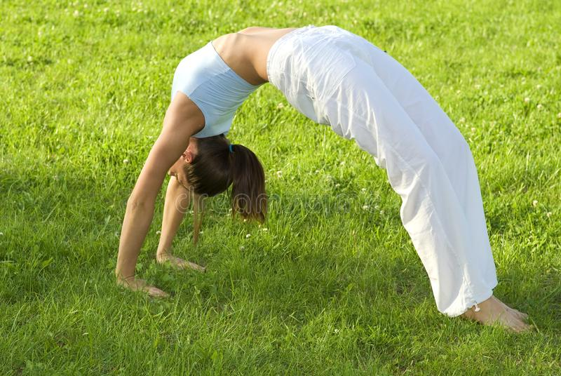 Sporty dziewczyna ćwiczy na łące przeciw niebu zdjęcie royalty free