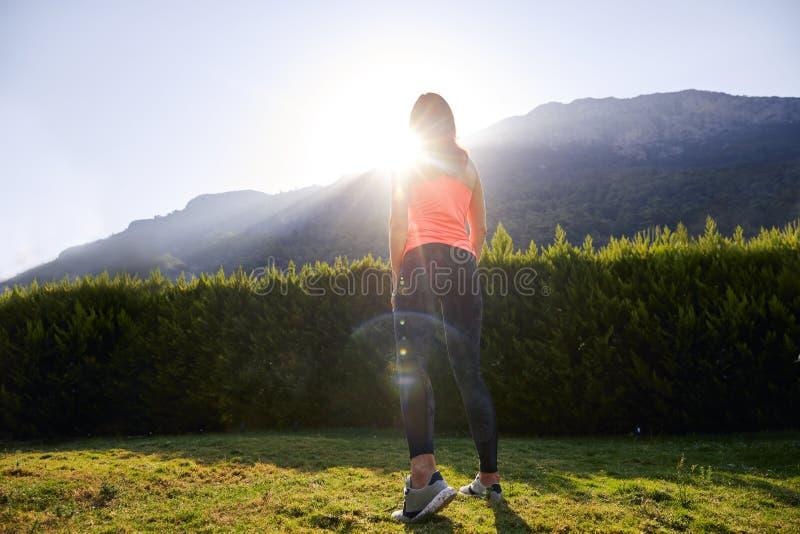 Sporty dziewczyna pełno energetyczna pozycja przeciw światłu słonecznemu zdjęcie stock