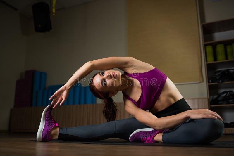 Sporty dziewczyna robi rozciąganiu na macie w sprawności fizycznej sali obraz royalty free