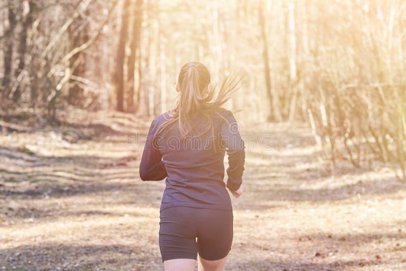 Sporty dziewczyna ucieka w drewnach od plecy zdjęcie royalty free