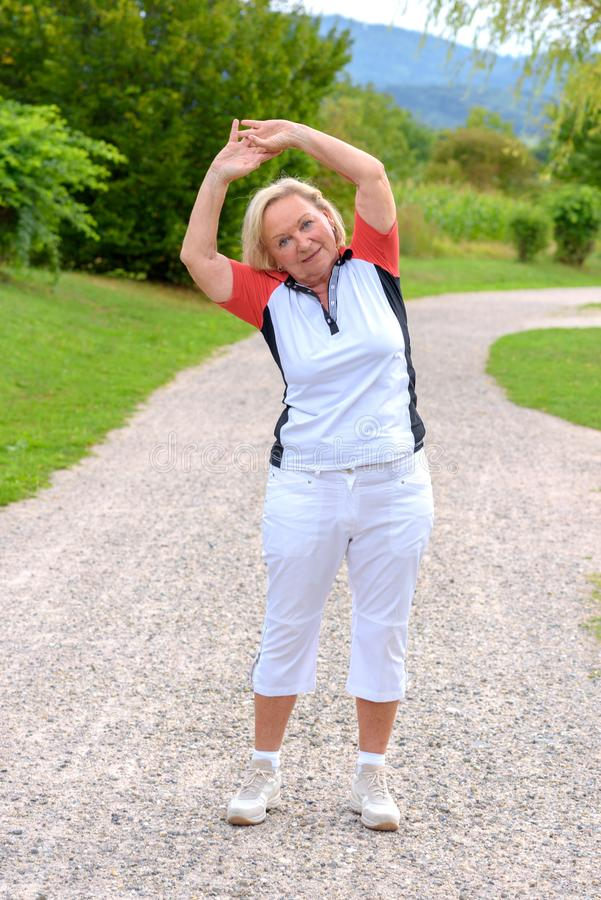 Sporty elderly woman doing sport exercises royalty free stock photography