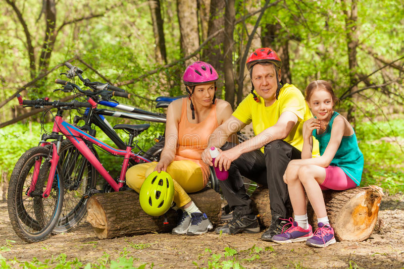 Sporty family refreshing after cycling in the wood. Sporty family refreshing after cycling, sitting on the logs in the sunny spring wood royalty free stock photography