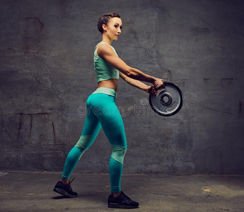 Sporty female working out with barbell weight over grey background. royalty free stock photos
