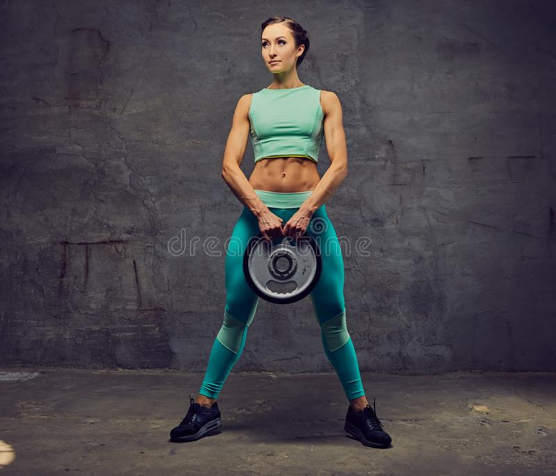 Sporty female working out with barbell weight over grey background. stock photo