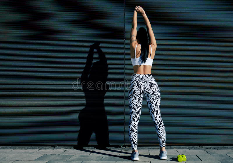 Sporty female in workout gear stretching before exercising outdoors. Back view portrait of young woman with perfect figure stretching her hands against black stock photography