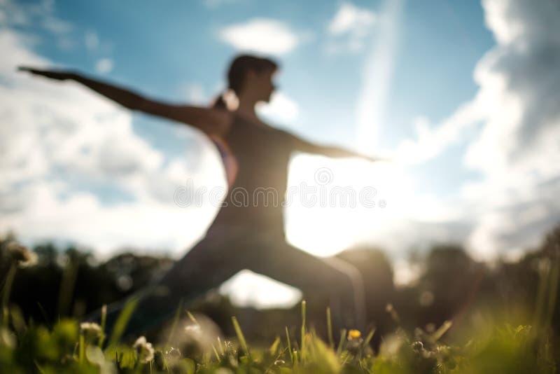 Sporty fit caucasian woman doing asana Virabhadrasana 2 Warrior pose posture in nature. Yoga outdoors. Sporty fit caucasian woman doing Ashtanga Vinyasa Yoga royalty free stock photography