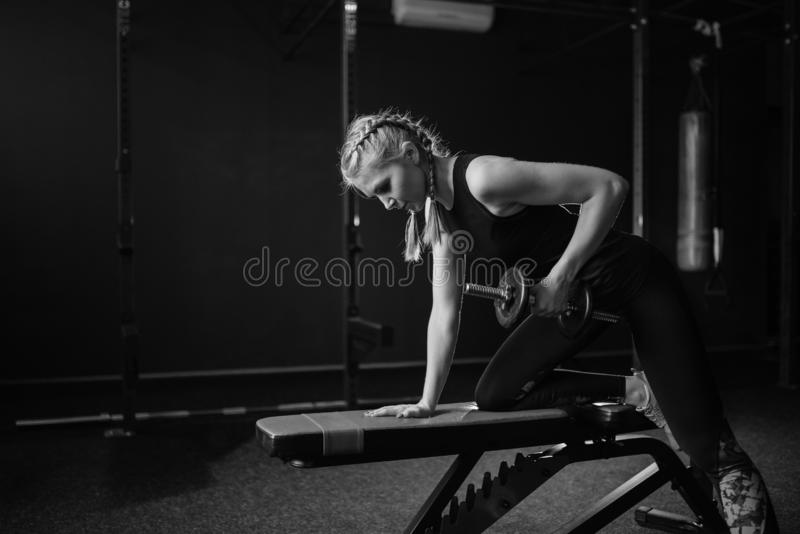 Sporty fit woman bodybuilder in gym lifting dumbbells on bench. Black and white. Copy space. Sporty fit woman bodybuilder in gym lifting dumbbells on bench stock image