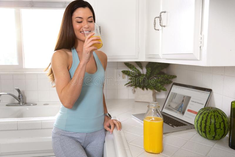 Sporty fit woman drinking fresh glass of orange juice in the morning, healthy lifestyle, fitness, exercise, wellness. Beautiful genuine lifestyle portrait of a royalty free stock photo
