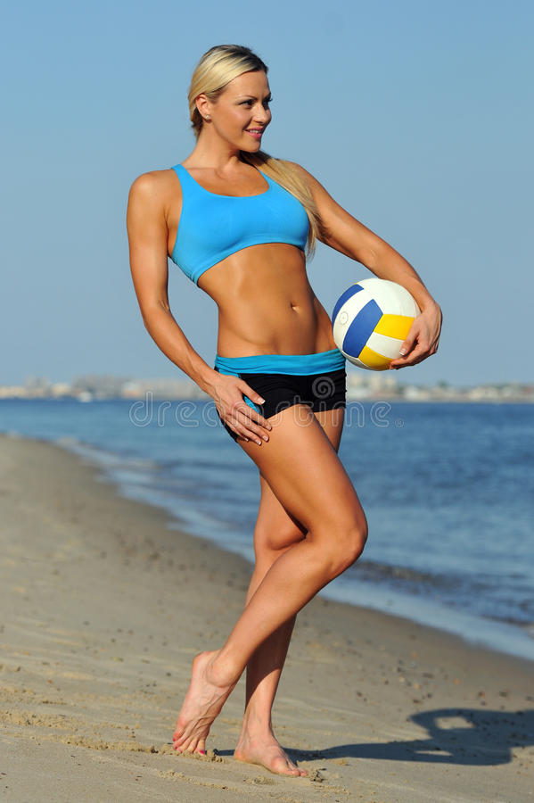 A sporty fit woman in her fitness clothes holding a volleyball ball. On the beach royalty free stock images
