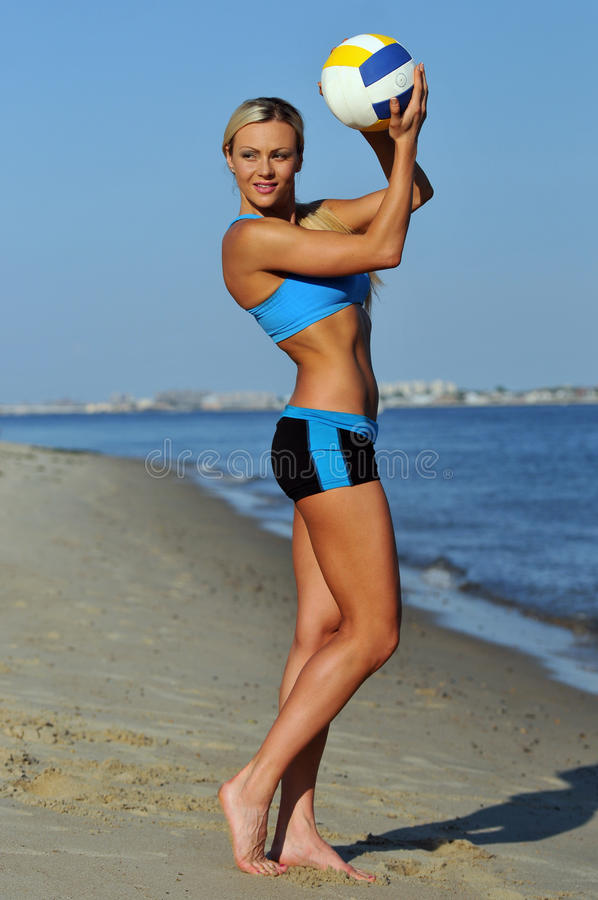 A sporty fit woman in her fitness clothes holding a volleyball ball. On the beach stock photos