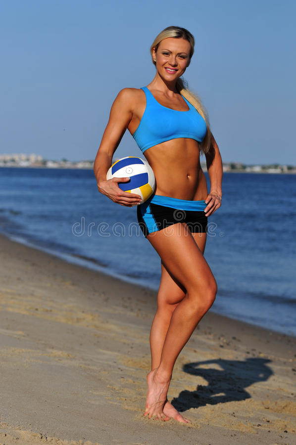 A sporty fit woman in her fitness clothes holding a volleyball ball. On the beach royalty free stock image