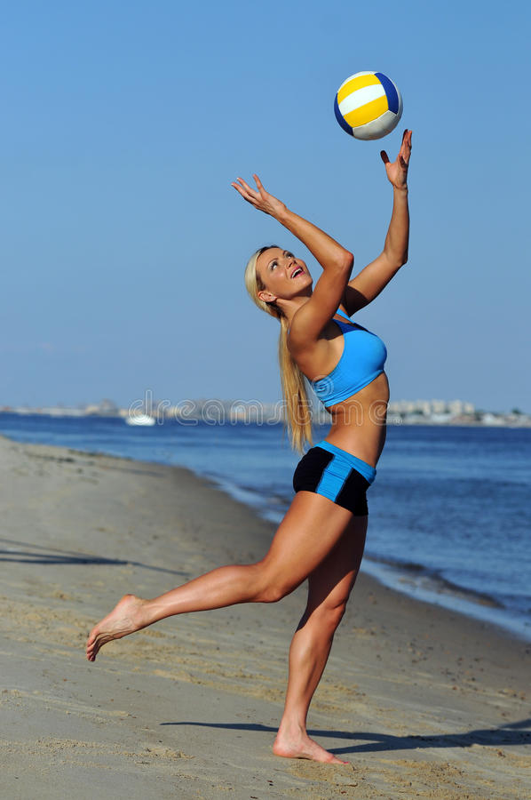A sporty fit woman in her fitness clothes playing volleyball royalty free stock images