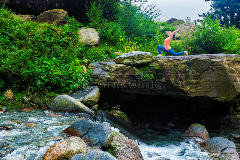 Sporty fit woman practices yoga Anjaneyasana in mountains royalty free stock image