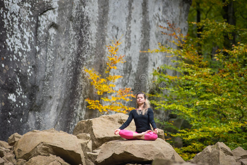 Sporty fit woman is practicing yoga on the boulder in the nature. Pretty flexible woman is practicing yoga and doing asana Siddhasana on the boulder in the royalty free stock photos