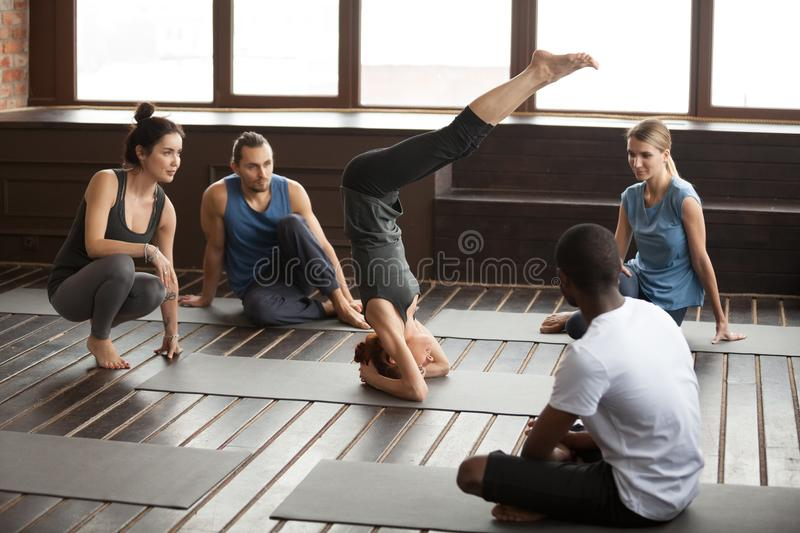 Woman standing on head practicing yoga at group training class. Sporty fit young women standing on head performing salamba sirsasana exercise, yogi girl doing royalty free stock image