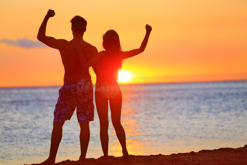 Sporty fitness couple cheering at beach sunset. Happy romantic fit young couple enjoying sunset with arms raised up flexing muscles together. People on sports royalty free stock image