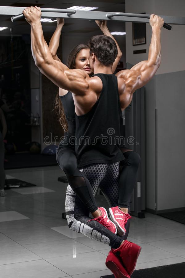 Sporty fitness couple doing pull up on horizontal bar in gym. Muscular man and woman pulling up, working out stock photos
