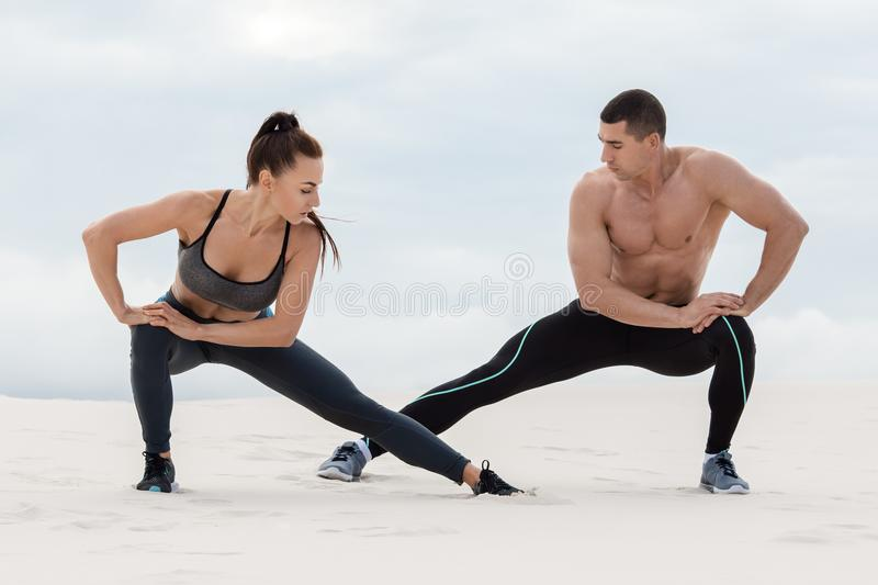 Sporty fitness couple doing stretching exercises outdoors. Beautiful athletic man and woman stock photography