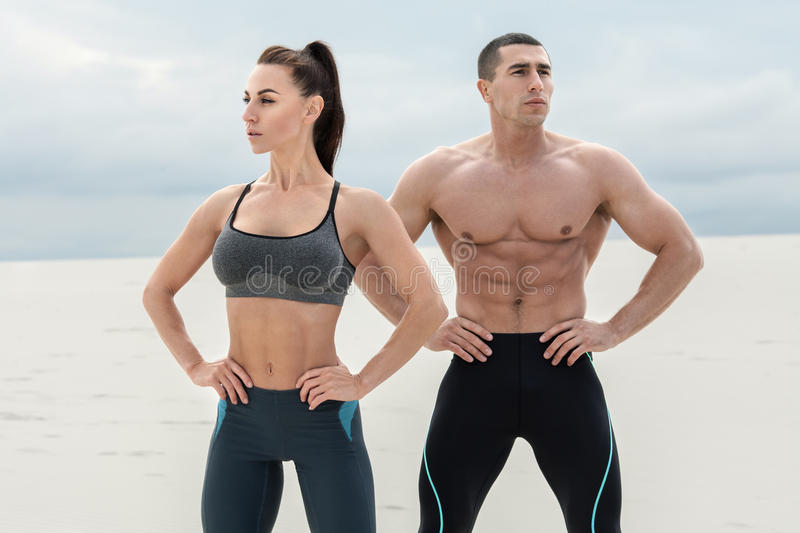 Sporty fitness couple showing muscle outdoors. Beautiful athletic man and woman, muscular torso abs royalty free stock images