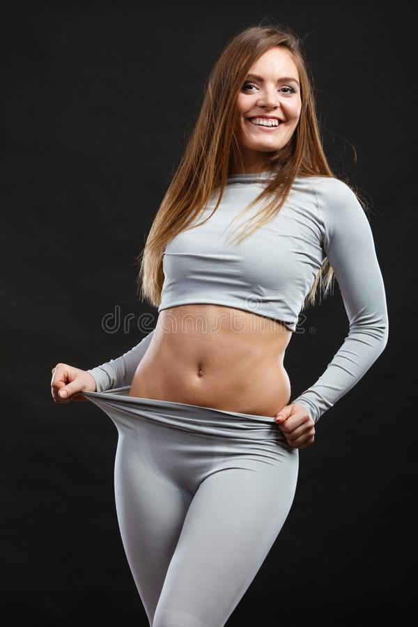 Sport fit woman in thermal clothes. Sporty fitness shape garments concept. Attractive lady in thermal clothes. Young seductive girl pulling shirt showing skin royalty free stock images