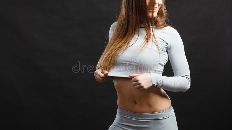 Sport fit woman in thermal clothes. Sporty fitness shape garments concept. Attractive lady in thermal clothes. Young seductive girl pulling shirt showing skin stock image