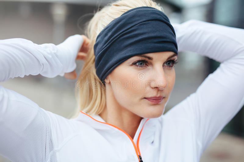 Sporty fitness woman on outdoor workout looking motivated. Close-up of young female athlete tying up hair before a run. Sporty fitness woman on outdoor workout stock photo