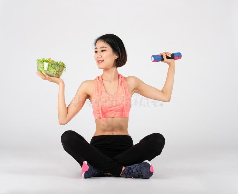 Sporty fitness woman in sportswear with vegetable salad dumbbell on white background. healthy sport stock photo