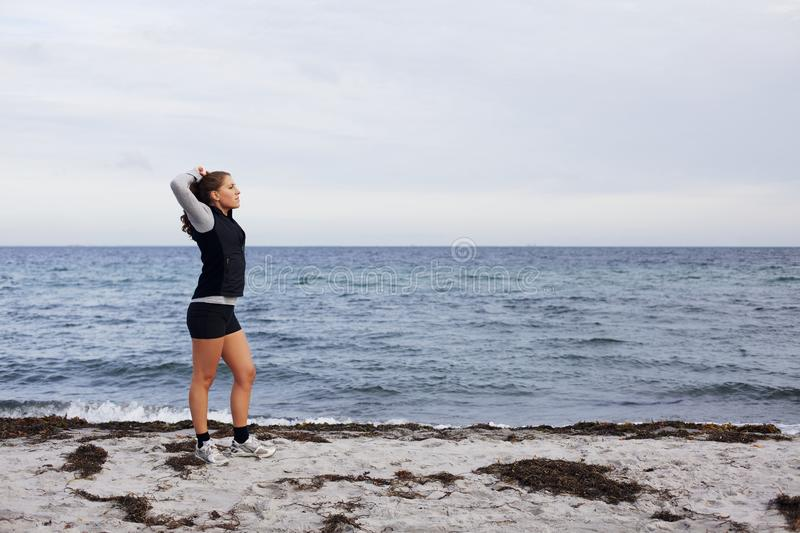 Sporty fitness woman standing on beach after workout. Looking away with hands behind head. Young female runner resting after jogging training on beach stock images