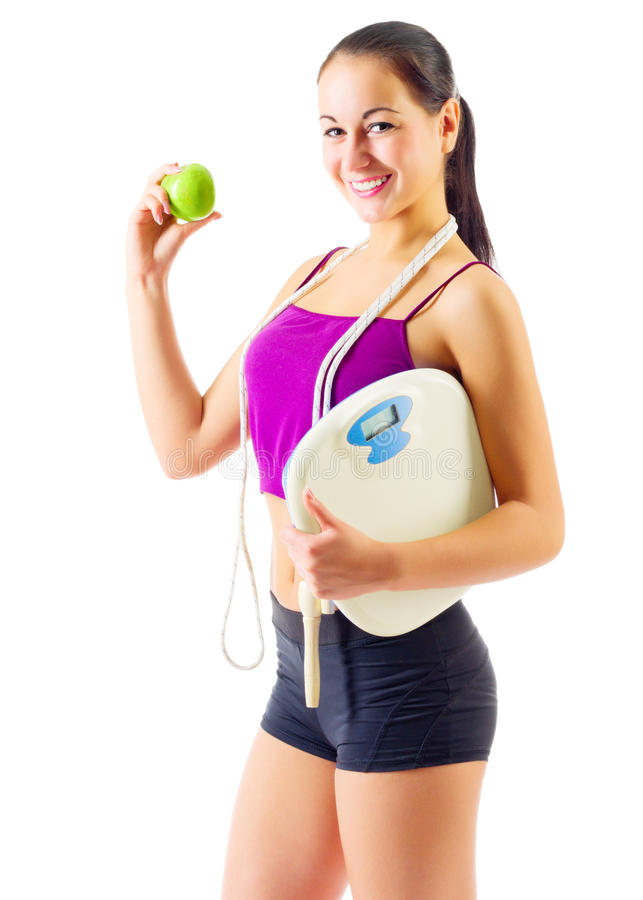 Sporty girl with apple and scales. Isolated royalty free stock photo