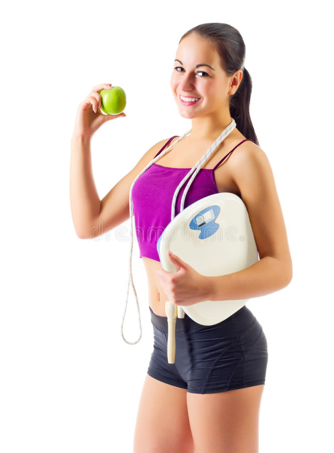 Sporty girl with apple and scales. Isolated royalty free stock photos