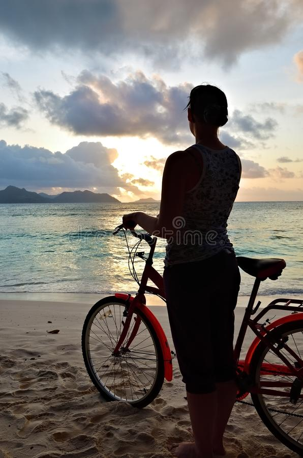 Sporty girl on the beach against sunset, Seychelles royalty free stock image