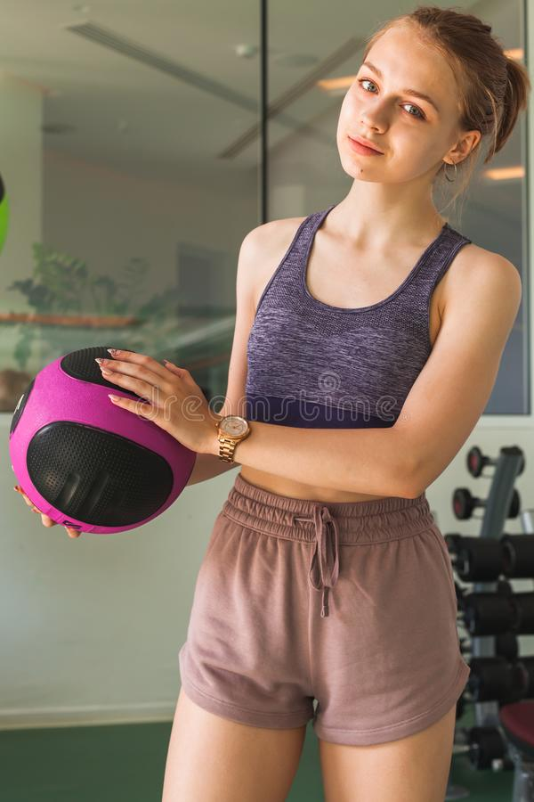 Sporty girl with black pink med ball in a gym. Young beautiful blond sporty girl with black pink med ball in a gym stock image