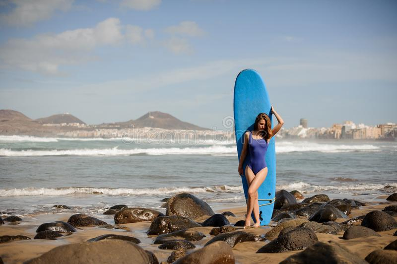 Sporty girl in the blue swimsuit standing against the surf stock images