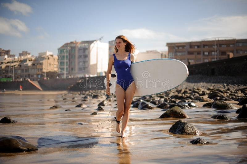 Sporty girl in the blue swimsuit walking with the white surfboard stock photo