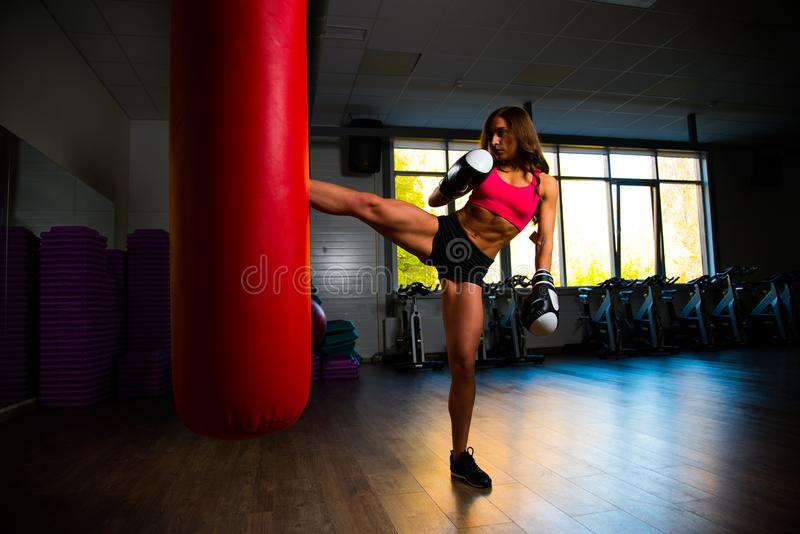 Sporty girl in Boxing gloves has his foot on bag. Photo royalty free stock photography