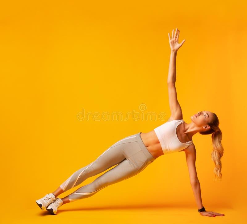 Sporty Girl, die während des Workout, beim Studio Shot eine Seitenteilung durchführen lizenzfreie stockfotos