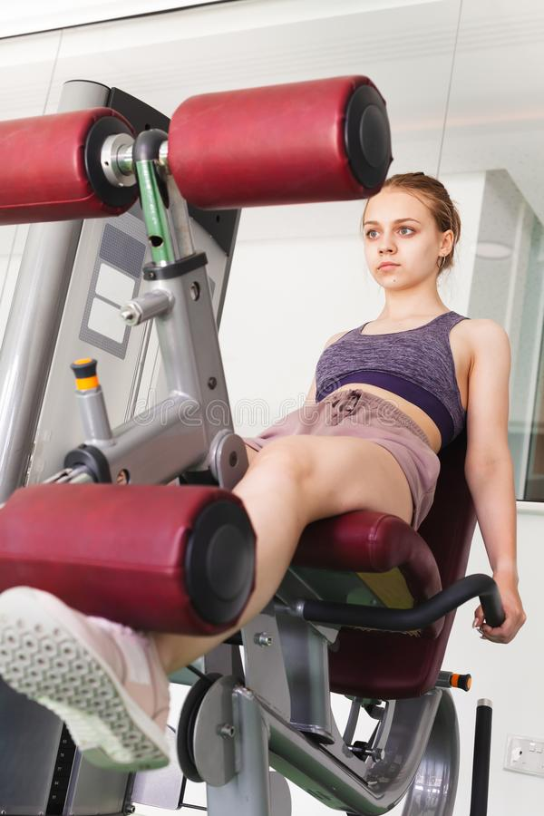 Sporty girl does a leg extension exercise royalty free stock image