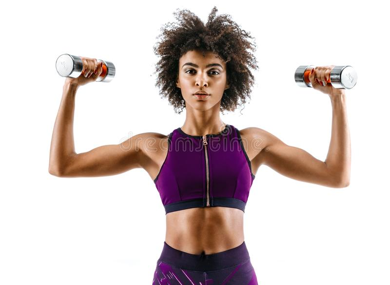 Sporty girl doing exercises with dumbbells. Photo of strong african girl isolated on white background. Strength and motivation royalty free stock photos