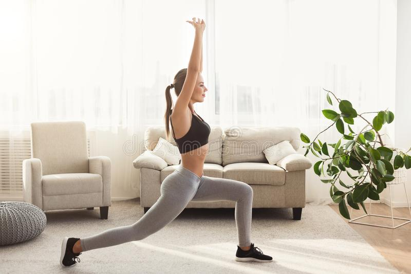 Sporty girl doing lunges exercise at home stock images