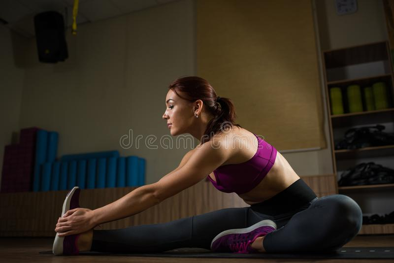 Sporty girl doing stretching on the mat in the fitness hall. stock photo