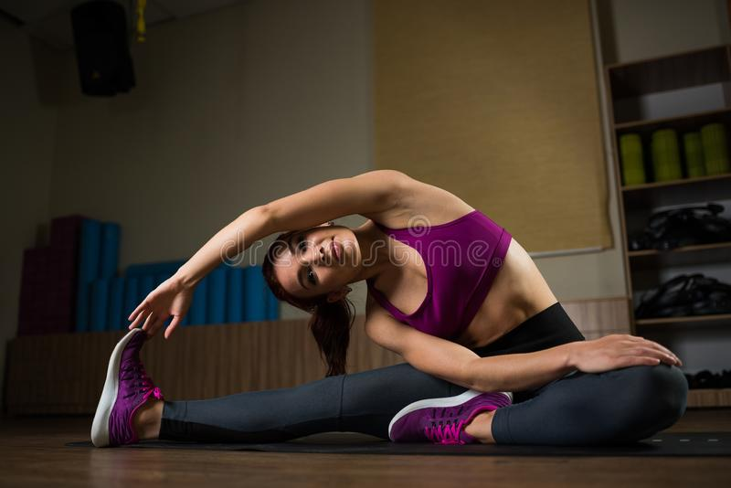 Sporty girl doing stretching on the mat in the fitness hall. royalty free stock photography